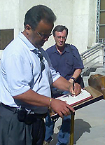 man signing guest book