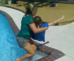 A woman performs CPR on a mock drowning victim