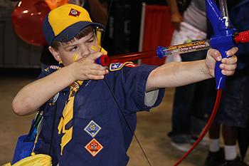 boy scout aiming an arrow