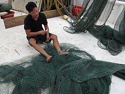 Mike Thinh Do, 47, repairs shrimping nets onboard the Lucky Star