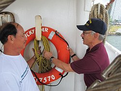 Gilbert Gallardo of the Coast Guard Marine Safety Unit explains to Captain Tran that the life ring should hang alone, free of other obstacles, for quick deployment when a man goes overboard