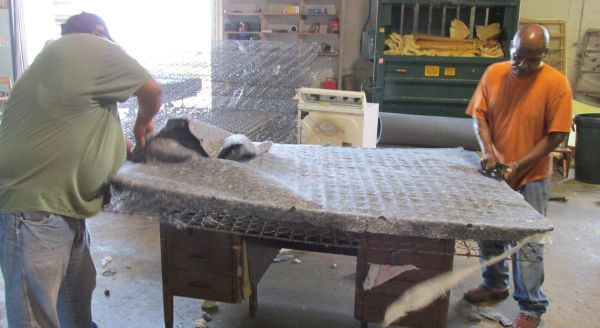 Two workers at the Houston Furniture Bank strip down a donated mattress