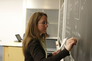a techer writes on a classroom chalkboard