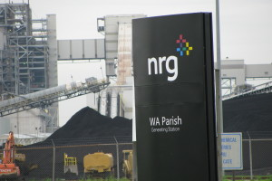 photo of NRG sign with coal mounds in background