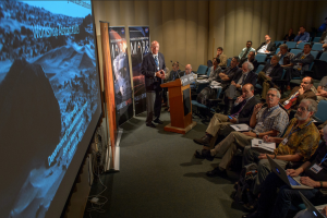 A presenter speaks at the conference while the audience views an image of Mars on a projector screen.