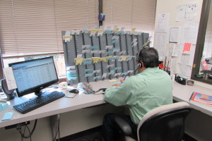 A dispatcher at Hour Messenger in Houston's Energy Corridor uses both a computer and index cards to keep track of deliveries.